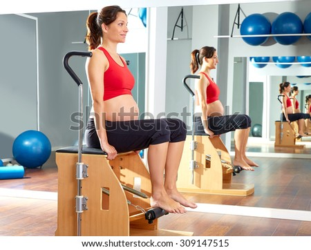 pregnant woman pilates leg pumps exercise on wunda chair - stock photo