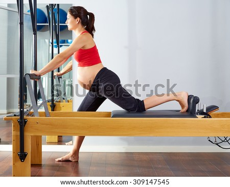 pregnant woman pilates reformer cadillac exercise workout at gym - stock photo