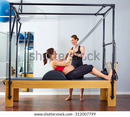 pregnant woman pilates reformer roll up cadillac exercise with personal trainer - stock photo