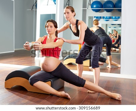 pregnant woman pilates side stretchs exercise workout at gym with personal trainer - stock photo