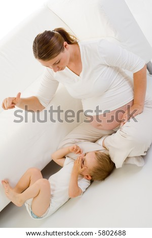 Pregnant woman playing with a toddler child. Angled view in mostly white.