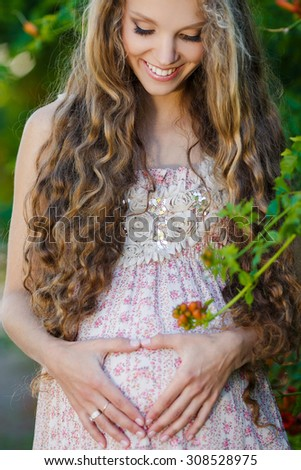 Pregnant woman posing in a green park. young happy pregnant woman relaxing and enjoying life in nature - stock photo