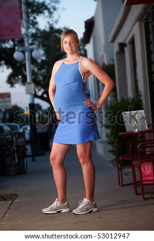Pregnant woman posing in fitness attire on the street - stock photo