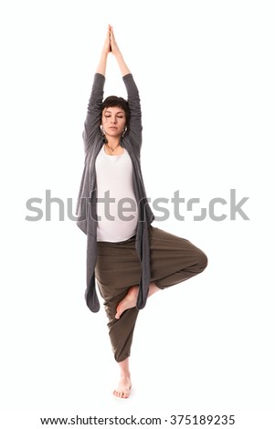 Pregnant woman practicing yoga, free gray casual clothing, white background studio shot of  fit Caucasian woman holding the vrksasana - stock photo