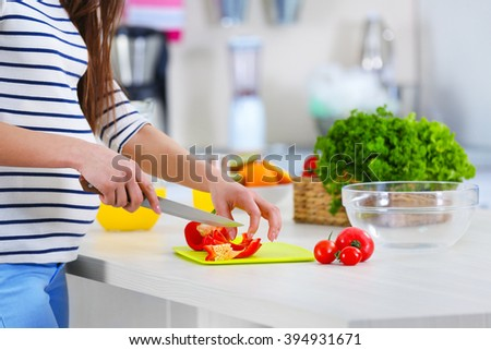 Pregnant woman preparing vegetable salad at table in the kitchen