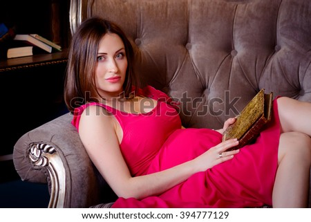 Pregnant woman reading a book lying on the couch - stock photo