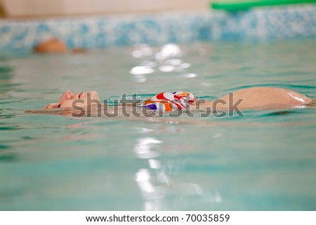 Pregnant woman relaxing in swimming pool during exercising - stock photo