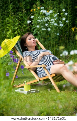 Pregnant woman relaxing in the garden