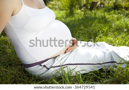 Pregnant woman relaxing in the garden - stock photo