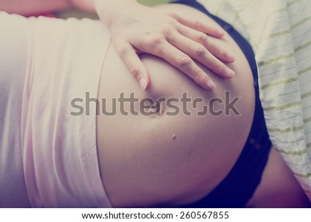 Pregnant woman relaxing on her back on a bed with her hand on her swollen bare belly as she bonds with her unborn baby, closeup view of her stomach and hand, toned retro effect. - stock photo