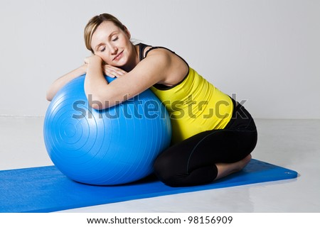 Pregnant woman relaxing while leaning against a fitness ball on a mat in a kneeling position - stock photo