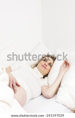 pregnant woman resting in bed - stock photo