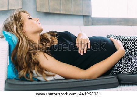 Pregnant woman resting on the bed in the bedroom and holding her hands on the belly - stock photo