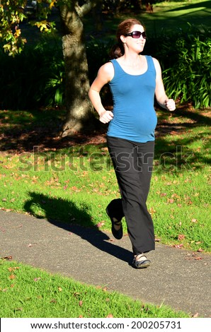 Pregnant woman run exercise during pregnancy outdoor at the park. Concept photo of women healthy life style and health care. copyspace - stock photo