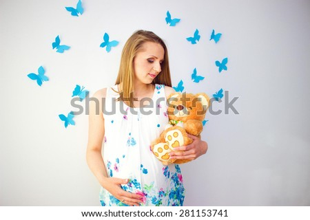 pregnant woman's belly with blue  butterflies over white background - stock photo