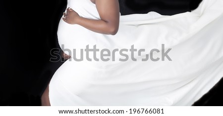 Pregnant woman's belly with flowing fabric - stock photo