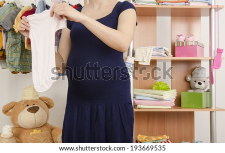Pregnant woman shopping for clothes for her newborn baby. Dressing closet with clothes arranged on hangers.Colorful wardrobe of newborn,kids, babies full of all clothes, shoes,accessories and toys - stock photo