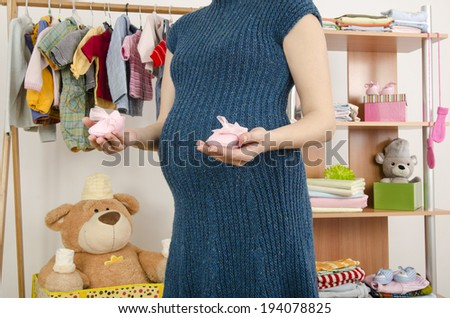 Pregnant woman shopping for clothes for her newborn baby. Dressing closet with clothes arranged on hangers.Colorful wardrobe of newborn, kids, babies full of all clothes, shoes, accessories and toys - stock photo