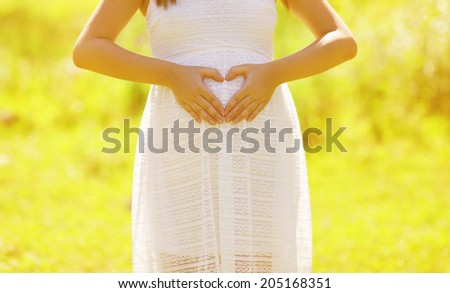 Pregnant woman showing hands in shape heart outdoors in sunny summer day - stock photo