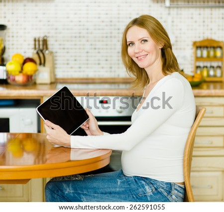 pregnant woman showing tablet computer - stock photo