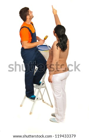 Pregnant woman showing to a painter man where to paint on the wall isolated on white background - stock photo