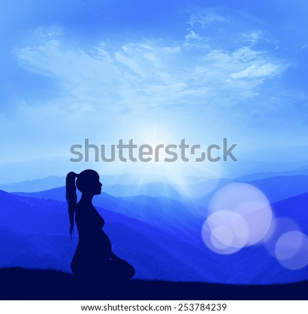 Pregnant woman. Silhouette on top of the mountain.