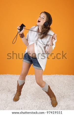 Pregnant woman sings along while listening to music on headphones - stock photo