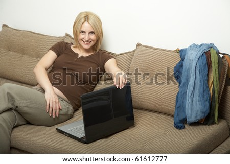 pregnant woman siting on a couch with laptop - stock photo