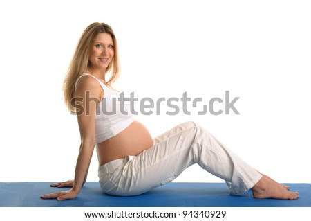 Pregnant woman sitting and practicing yoga isolated on white - stock photo