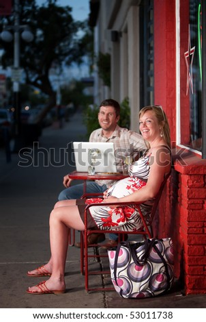 Pregnant woman sitting at a cafe with her male partner - stock photo