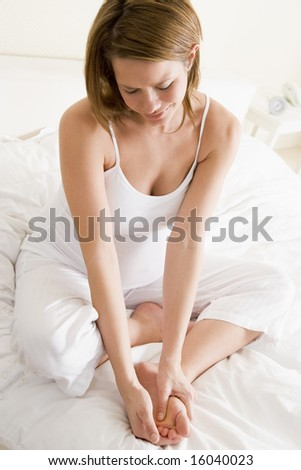 Pregnant woman sitting in bed smiling and rubbing feet
