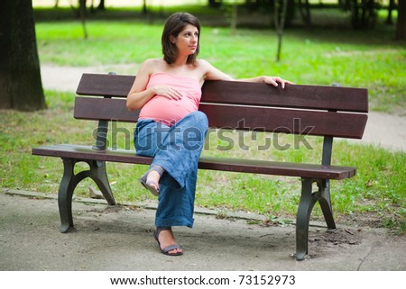 Pregnant woman sitting on bench after a walk in nature - stock photo