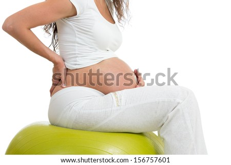 pregnant woman sitting on fit ball with hand on her back, isolated - stock photo