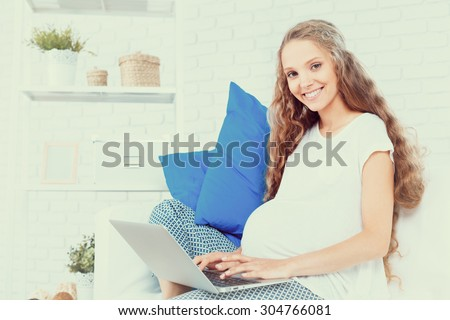 Pregnant woman sitting on sofa and looking at laptop - stock photo