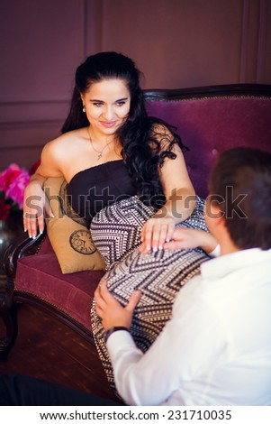 pregnant woman sitting on the couch and holding the hand of her husband - stock photo