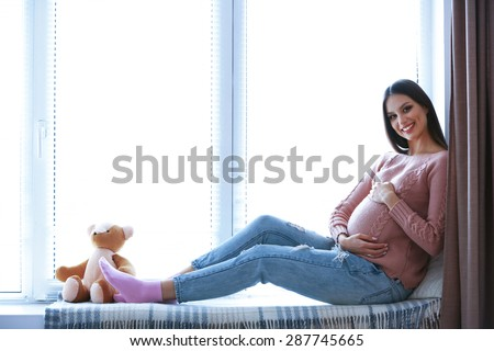 Pregnant woman sitting on windowsill background - stock photo