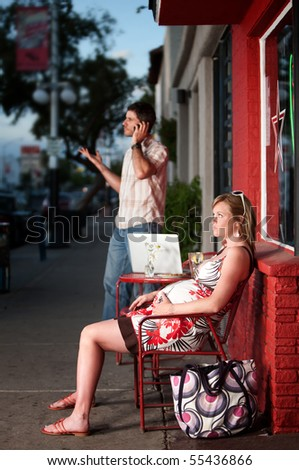 Pregnant woman sitting outside being ignored by partner - stock photo