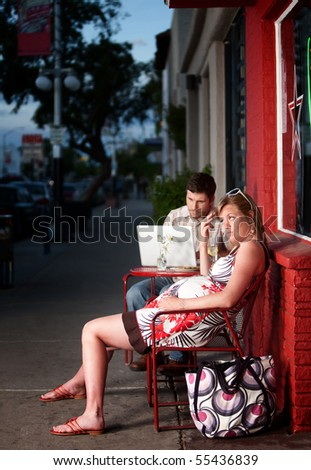 Pregnant woman sitting outside with annoying partner on computer next to her - stock photo