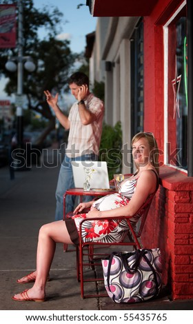 Pregnant woman sitting while man talks on his phone - stock photo
