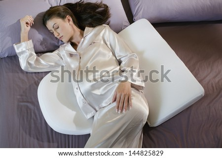 Pregnant woman sleeping with maternity body pillows - stock photo