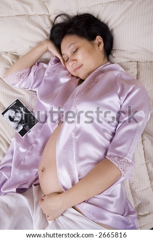 Pregnant woman sleeping with the ultrasound picture sitting next to her