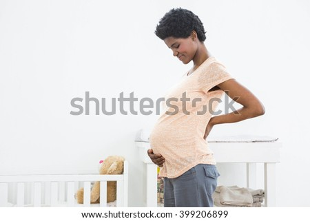 Pregnant woman standing near cradle and smiling while looking at her stomach - stock photo