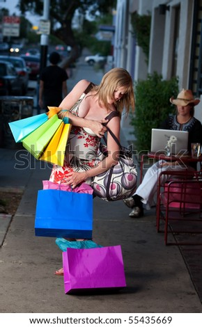 Pregnant woman struggling with multiple shopping bags - stock photo