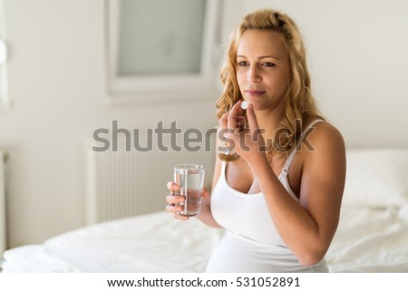 Pregnant woman taking medication pill