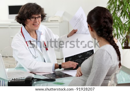 pregnant woman visiting her doctor - stock photo