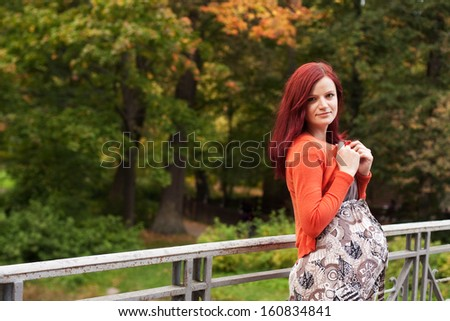 pregnant woman walking in autumn park