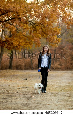 Pregnant woman walking in the woods with the dog