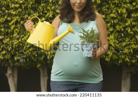 Pregnant woman watering potted plant outdoors - stock photo