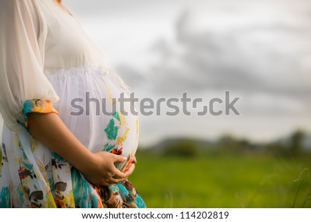 Pregnant woman wearing floral white dress affectionately holding her belly outside with newly planted rice field and cloudy sky in background. - stock photo
