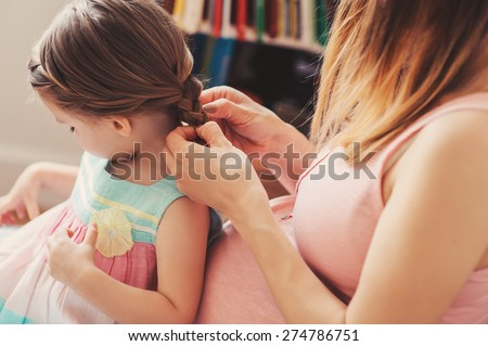 pregnant woman weaving braids with her toddler daughter at home - stock photo